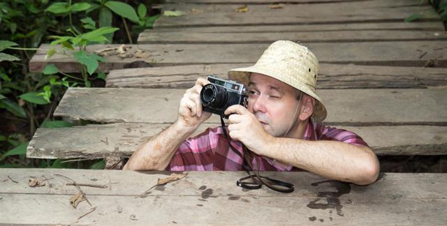 Tourist mit Fotoapparart, der in Loch in der Brücke gestürzt ist